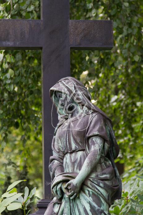 Trauernde an Grabkreuz