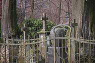 Grabkreuze hinter Metallzaun