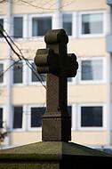 Grabkreuz vor Hochhaus