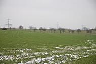 Schneespuren auf grünem Acker