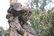 Frauenfigur trägt Kreuz